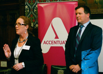 Jo Nolan and Damian Collins standing facing forwards giving a speech with the Accentuate banner behind them, in the highly decorative room with wooden panels in the Houses of Parliament